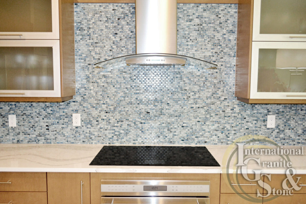 Cambria Quartz Brittanicca Countertops Island Stainless Steel Hood Cooktop  Blue Tile Mosaic Backsplash White Kitchen Marble